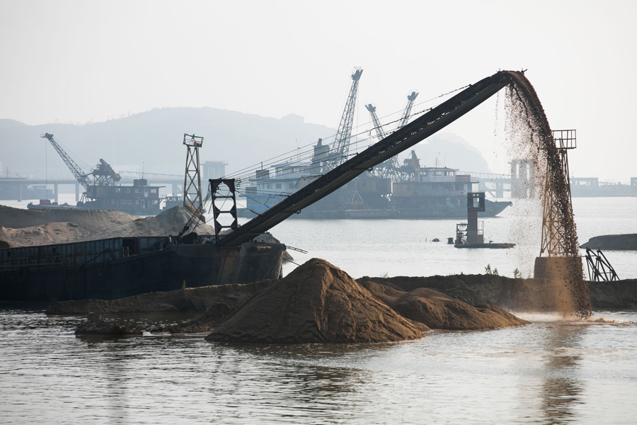 Sand boats operate in Poyang Lake in Jiujiang, Jiangxi province on April 28. Excessive sand mining is believed to have caused damage to the eco-system. Photo: Visual China