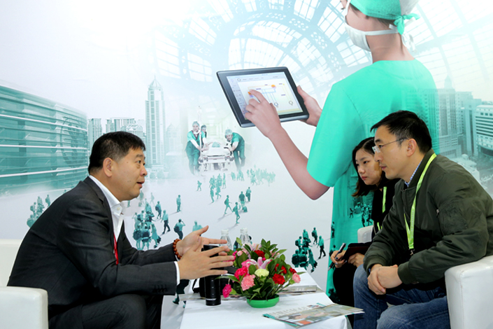 An exhibitor at the 5th China International Medical Tourism (Beijing) Fair explains his company's products to potential consumers. The fair opened on Nov. 18. Photo: Visual China