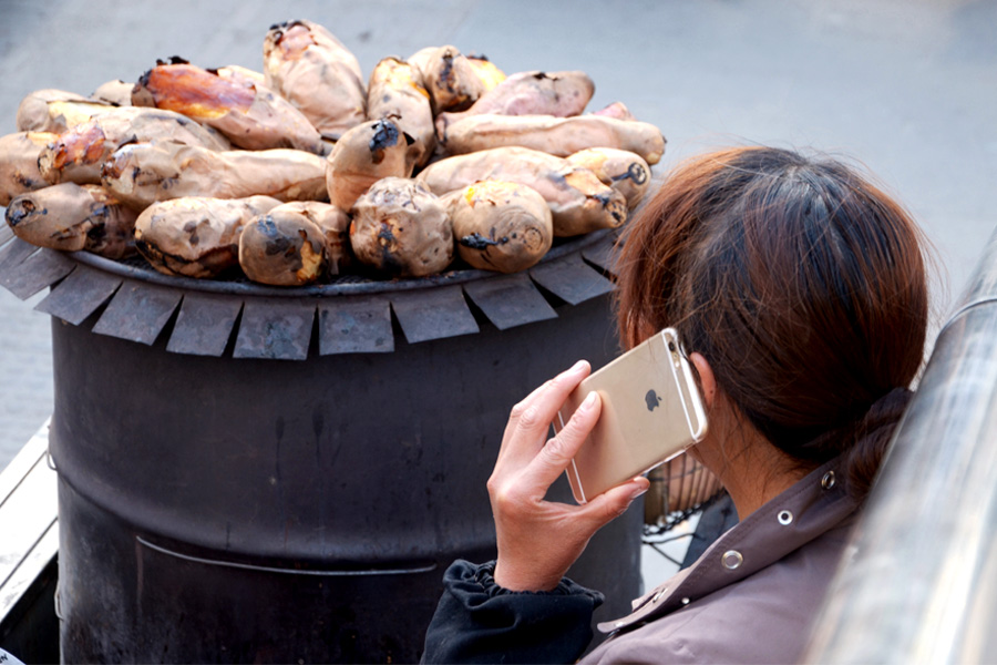 Caption: A street vendor selling sweet potatoes makes a phone call with his iPhone in Beijing's Chaoyang district on Mar. 31. Photo: IC