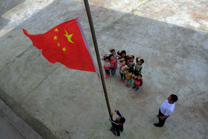 Wu Guoxian (right) and some of his students attend a flag-raising ceremony in Gugang Primary School in Qiannan prefecture, Guizhou province, on May 31. The rural school has only 11 students, and Wu, 50, is its only teacher. He also fills other roles at the school, including cook and cleaner. Photo: Visual China
