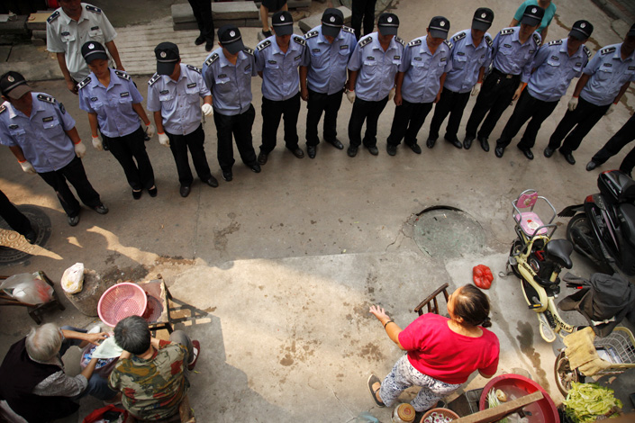 A line of city management officers, known as chengguan, stare in silence at an illegal street vendor selling vegetables in Wuhan, Hubei province, on Sept.19, 2012. Critics of the harsh enforcement want chengguan to change their enforcement style. Photo: IC