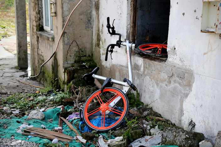 A broken Mobike lies in a residential community in Shanghai's Putuo district on Nov.28. As Mobike and Ofo shared bicycles, which can be unlocked with a smartphone app and left anywhere after use, have become popular in many large cities, more of the bicycles are being stolen and sold online. Photo: Visual China
