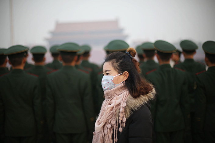 A woman wearing a face mask walks through Tiananmen Square in Beijing amid heavy smog on Nov. 26. Beijing city authorities declared this year's first