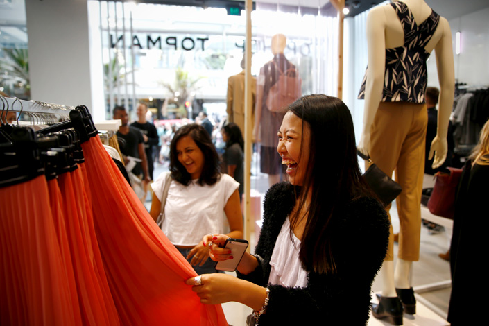 Shoppers look through clothes on sale on the opening day of New Zealand's first Topshop and Topman store on March 12, 2015, in Auckland, New Zealand. A British high-end brand beloved by celebrities, Topshop opened its first official physical store in Beijing on Aug. 28, 2015, at the Galeries Lafayette mall. Photo: Visual China