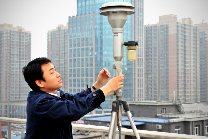 An environmental official collects PM2.5 data through an air-quality monitor facility in Beijing in January 2012.   Photo: IC