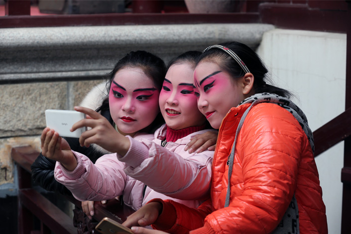 Young participants of an Peking Opera contest take a selfie on the sidelines of the event in Nantong, Jiangsu province, on Dec. 10. Many people in China share their photos on social media platform WeChat. Photo: Visual China