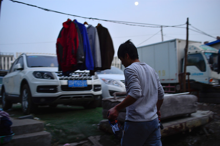 Zhang Jianwei, who doubles as a Didi driver and home-moving worker, hangs his laundry in a yard near his home in northwestern Beijing on Nov. 13. Photo: Yang Yifan/Caixin