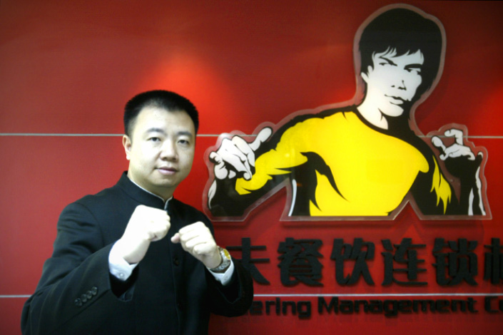 Cai Guobiao, the then-chairman of Guangzhou Real Kungfu Catering Management Co. Ltd., poses near the company's logo in May 2008. Photo: IC
