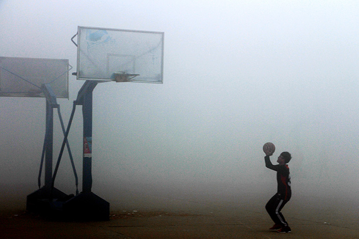 A student plays basketball during a hazy day in Liaocheng,Shandong province, on Dec. 23, 2015. Education authorities in Beijing have picked 13 primary schools for a pilot program in which classrooms will get ventilation system to fight smog. Photo: IC