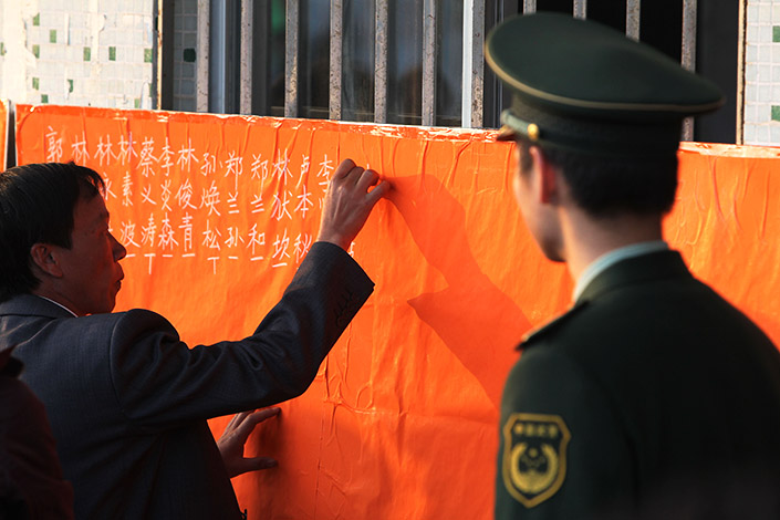 A police officer watches votes being counted after a village committee election in Wukan, Guangdong province, in February 2012. Supreme People's Procuratorate President Cao Jianming vowed over the weekend to crack down on rural village officials who abuse their power to grab land and force residents from their homes. Photo: Wu Jiang/Visual China