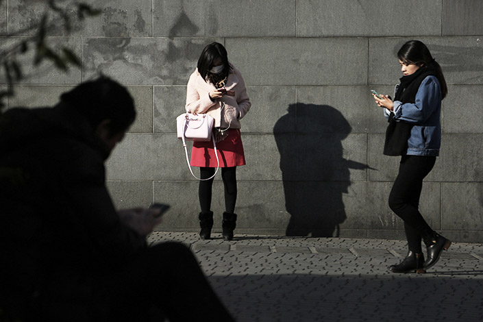 Pedestrians use their cellphones on a public square in Shanghai on Dec.17, 2015. The number of Chinese internet users grew 6.2% last year to 731 million, of which 95% are smartphone users. Photo: Visual China