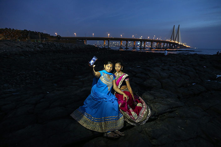 Two women pose for a selfie at a tourist spot near the Arabian Sea in Mumbai, India, in February 2016. According to a research report, Chinese brands captured close to 50% of India's smartphone market share last year, up from 14% in 2015.  Photo: IC