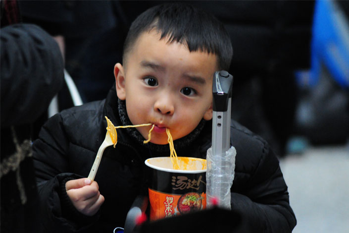 Yang Zhenting, 4, eats instant noodles while waiting with his mother at a railway station in Hangzhou, Zhejiang province, on Jan. 16. Millions of migrant workers rushed home to celebrate the Chinese New Year, which began on Saturday. Photo: IC