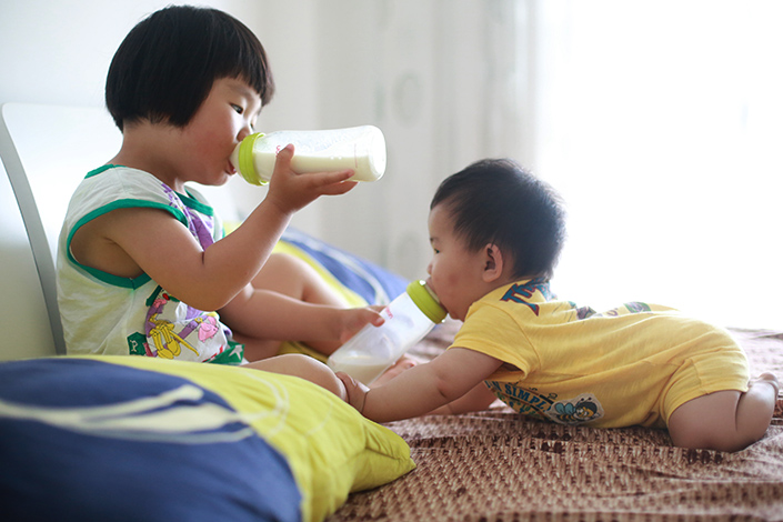 A girl feeds her little sister and herself at the same time in Taizhou, Zhejiang province, in May 2013. Families in Zhejiang receiving court orders to pay overdue fine for the second child before 2014 are saying they shouldn't have to pay as the one-child policy was abolished at the end of 2015. Photo: Visual China
