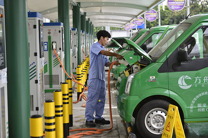 A man charges a new-energy car in Shenzhen, Guangdong province, on July 14. China's Automotive Industry Group wants to see lower production quotas for new-energy vehicles from 2018 to 2020. Photo: Visual China