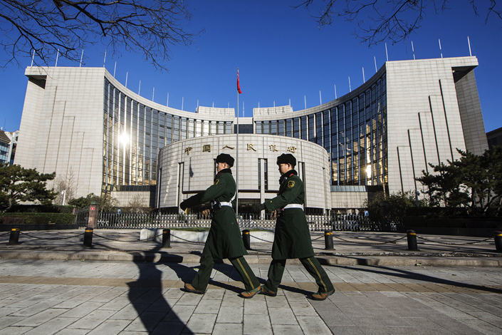 People's Liberation Army soldiers march past the People's Bank Of China headquarters in the financial district of Beijing in December 2015. China's financial regulators are embarking on what's likely to be a long and hard-fought battle to bring the unwieldy 100 trillion yuan ($14.6 trillion) asset management industry under control. Photo: Visual China