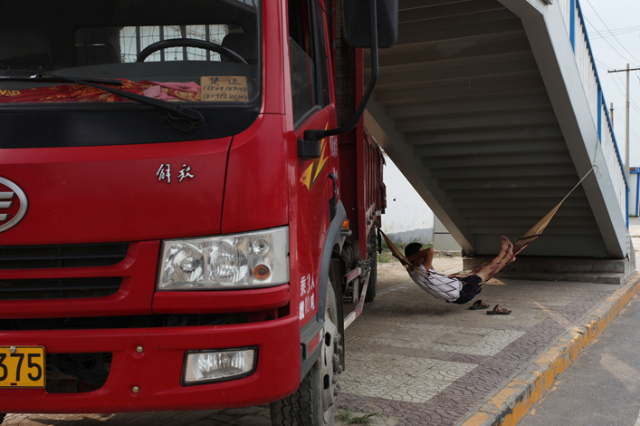 A truck driver relaxes in the shade of a bridge while waiting for freight business outside a wholesale market in Xi'an province in July 2013. Smartphone apps are revolutionizing China's trucking industry, as technology supplants a system that had depended on chalkboards. Photo: Visual China