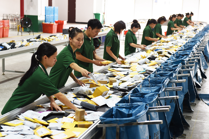 Workers at the cross-border e-commerce branch of China Post in Yiwu, Zhejiang province, sort parcels in July. The Chinese government has unveiled new delivery guidelines for the state-owned enterprise, which is struggling to compete with faster, more-convenient delivery services. Photo: Visual China