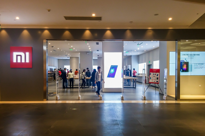 Customers try out electronic products at a Xiaomi store in Shanghai on May 13. Xiaomi Inc. plans to build more than 1,000 brick-and-mortar stores over the next three years as it abandons its online-only sales model. Photo: IC