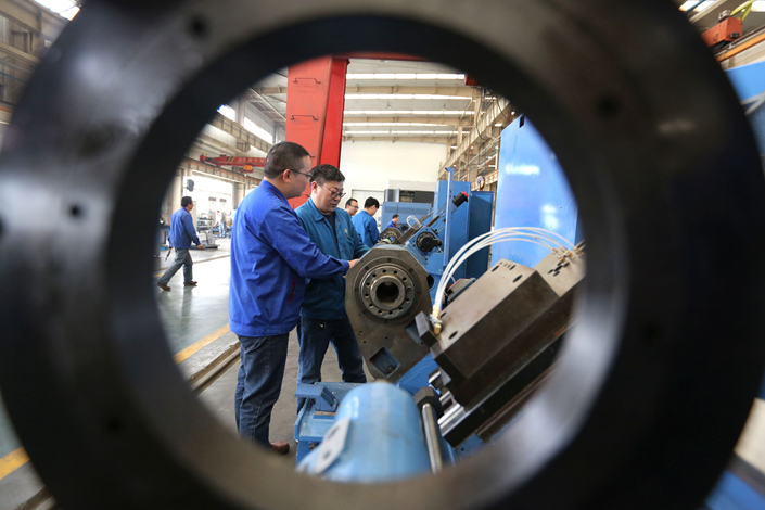 Workers assemble machine tools at a machine-tool company in Henan province on April 20. Recent bond defaults of China's largest machine-tools producer are a reflection of the pressures facing the machinery, coal and steel sectors. Photo: IC