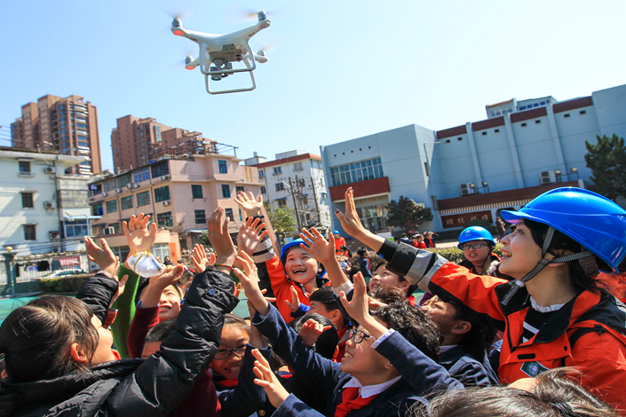 Children watch a drone demonstration in Wenzhou, Zhejiang province, on March 2. China is considering requiring real-name registration of drones, which until now have been loosely regulated. Photo: IC