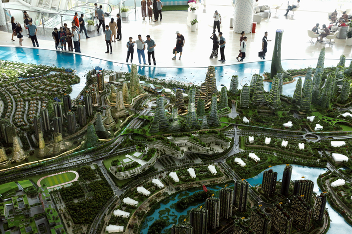 Prospective homebuyers examine a model of Country Garden Group's planned Forest City development in a showroom at Johor Bahru, Malaysia, on Feb. 21. Country Garden said China's restrictions on capital outflows had nothing to do with its decision to idle mainland sales centers for the development. Photo: Visual China