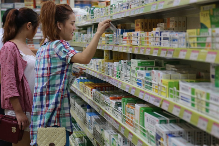 Women shop in a pharmacy in Xuchang, Henan province, on Aug. 17, 2013. A draft law allowing multinationals to conduct clinical trials in China before getting approval at home is likely to shakeup China's domestic drug market.  Photo: Visual China