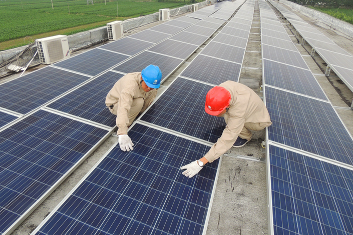 Photovoltaic power generation solar panels are inspected in Lianyungang, Jiangsu province, on July 19. Wasted energy from wind and solar projects in China was 46.5 billion kilowatt-hours last year. Photo: Visual China