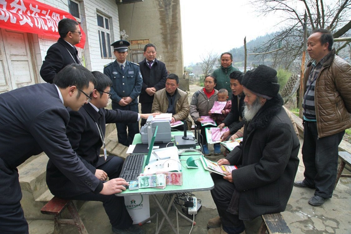 Employees of Rural Credit Cooperatives, carrying teller machines, a printer and other equipment, visit a remote village to provide financial services to villagers, in Guiyang, Guizhou province, on March 2. Bank of Guiyang President Li Zhongxiang has proposed easing restrictions that require bank customers to visit a branch in person and have their ID verified to open an account. Photo: IC
