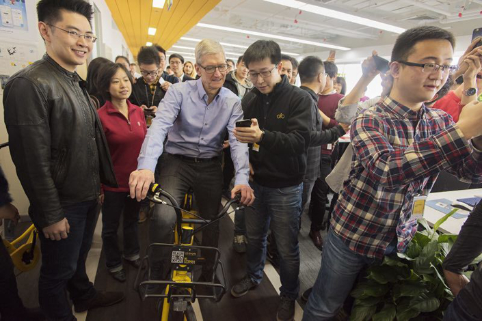 Apple CEO Tim Cook (center) visits the bike-sharing start-up Ofo in Beijing on Tuesday. Photo: Apple