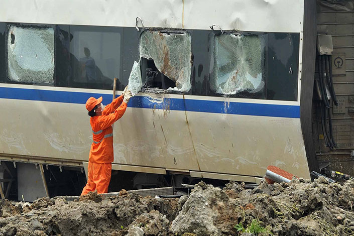 A worker removes a broken window after a train accident in Wenzhou, Zhejiang province, on July 26, 2011. The number of people killed in railway accidents has been declining in the past six years. Photo: Visual China