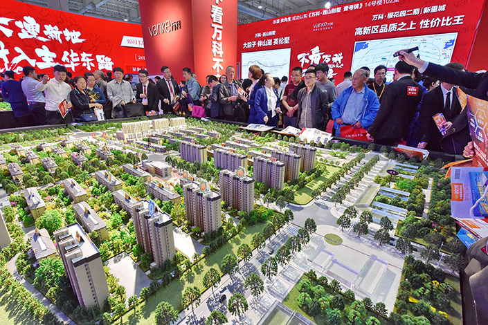 Visitors look at a real-estate model at the Dalian Autumn Housing Fair on Oct. 14, 2016. Some people are no longer able to afford to buy a home after a recent policy change in Beijing. Photo: IC