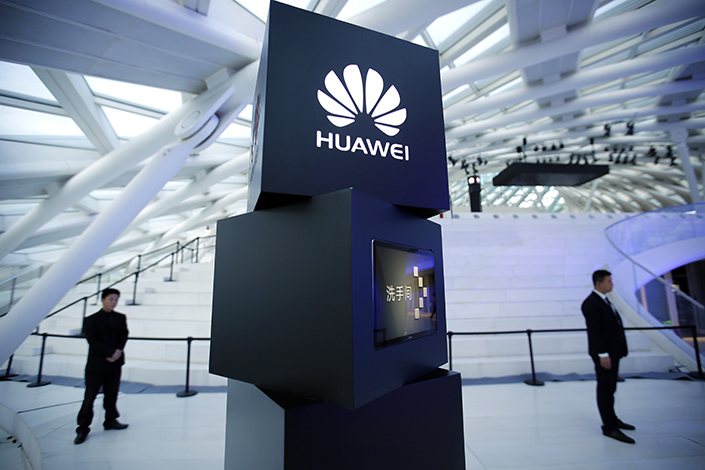 Security personnel stand near a podium at a launch event for the Huawei Mate Book in Beijing. Photo: IC