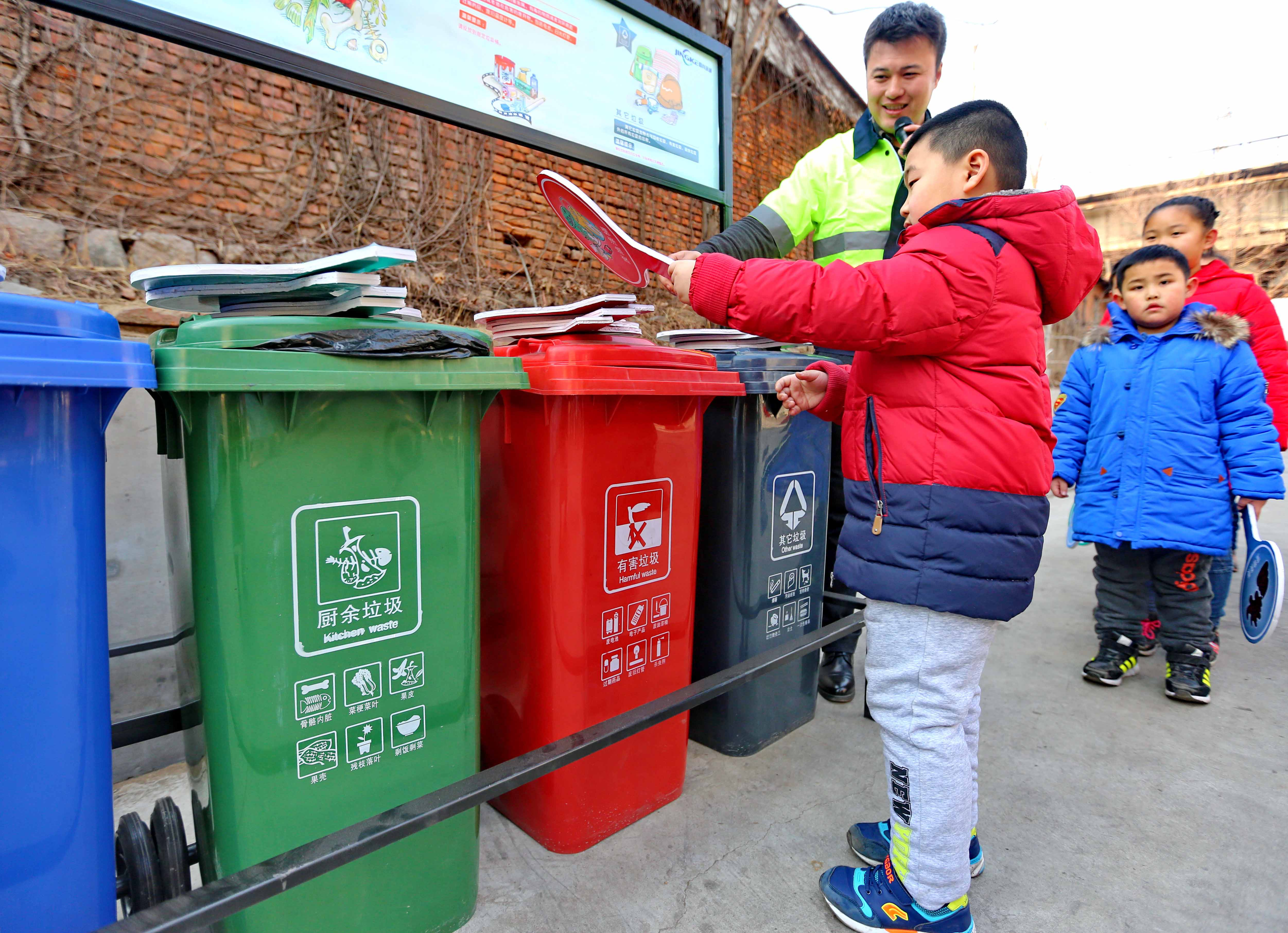 A community worker teaches children to sort waste during an awareness campaign in February in Qinhuangdao, Hebei province. Photo: IC
