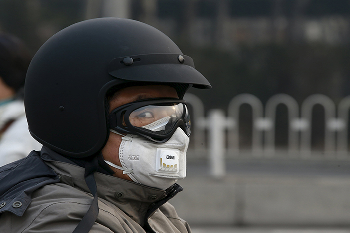 A man wearing a mask rides a motorcycle during a red alert for air pollution, in Beijing, China, on Dec. 20, 2015. Beijing declared an orange alert Monday, meaning that the Air Quality Index is forecast to be over 200 for three straight days. Photo: Visual China