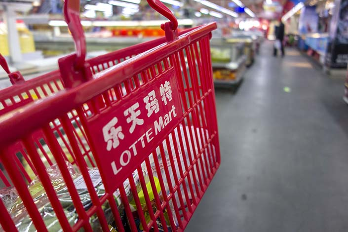 A customer carries a shopping basket in a Lotte Mart in Beijing on March 2. Seventy-five of Lotte Mart's 99 China stores have been closed since the South Korean retailing giant agreed to provide Seoul with a golf course to use as the site of an anti-missile system. Photo: Visual China