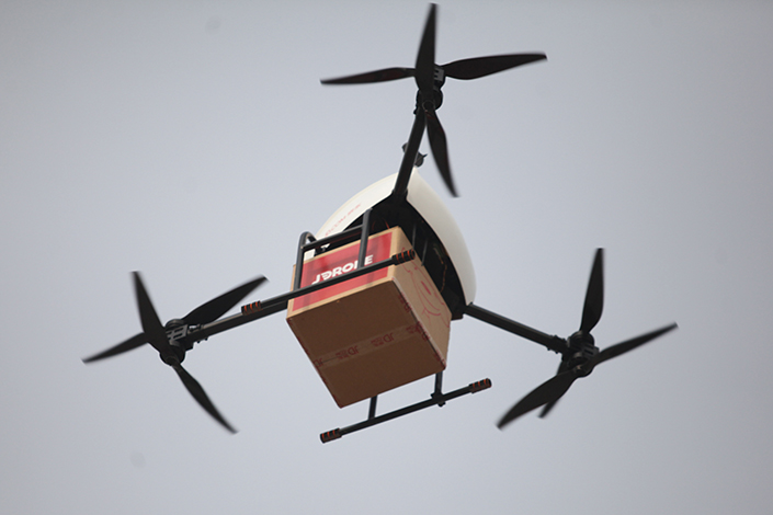 A drone carrying a parcel belonging to online retailer JD.com hovers over Xian, Shaanxi province, during a trial run on Nov.10, 2016. Photo: IC