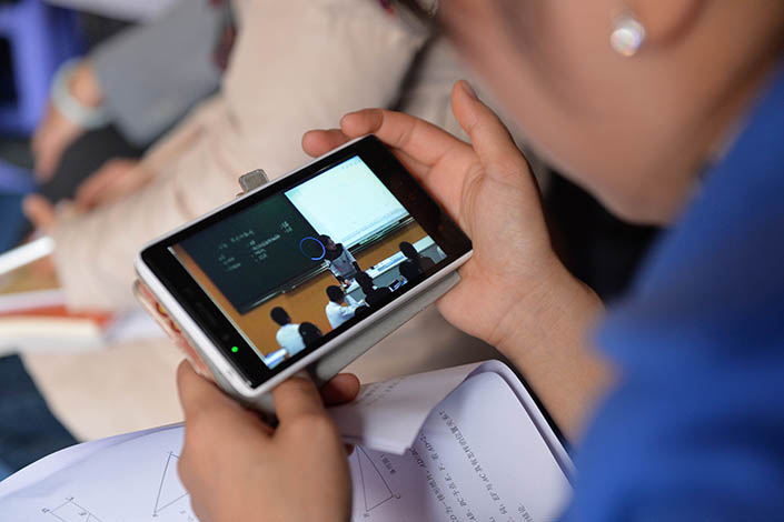 A junior high school mathematics teacher uses a mobile phone to watch a live-stream class via  WeChat in Shanghai on Nov.30,  2015. Photo: Visual China