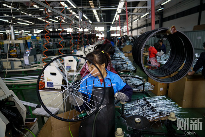Workers assemble shared bicycles in a manufacturing workshop in Tianjing on March 11. Photo: Yang Yifan/Caixin