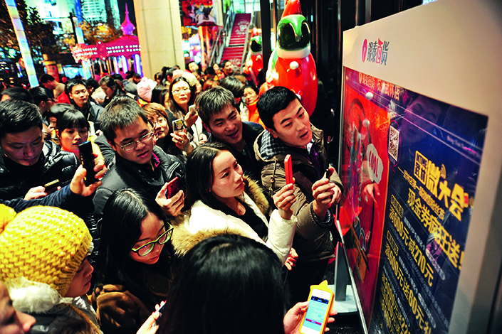 Shoppers scan a promotional QR code in front of an Intime department store in Hangzhou, Zhejiang province, on Dec. 31, 2013. Major department stores in China saw their revenues increase by 2% to 8% in the first two months of 2017, significantly better than the first quarter of 2016. Photo: Visual China