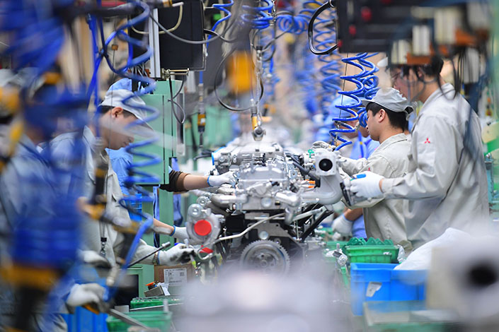 Workers assemble engines on the production line of Mitsubishi Motors Corp. plant in Shenyang, Liaoning province, on Feb.20. A new report says that the manufacturing sector and information technology are replacing natural resources as favorite overseas investment targets for Chinese state-owned and private companies. Photo: IC