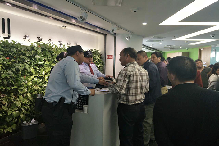 Yidao Yongche drivers descend on the company's headquarters in Beijing on Tuesday to demand payment. Drivers with the ride-hailing company have been complaining for several months that they have had difficulty transferring money out of their company accounts. Photo: Liu Xiaojing/Caixin