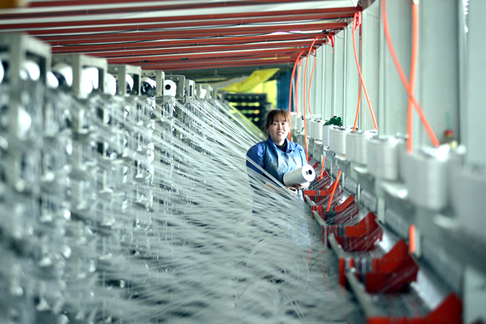 The International Monetary Fund raised its projection for China's economic growth in 2017 to 6.6%, but warned that the country's reliance on debts could present serious problems in the long term. Above, A worker makes plastic bags in a company in Suihua, Heilongjiang province. Photo: Visual China