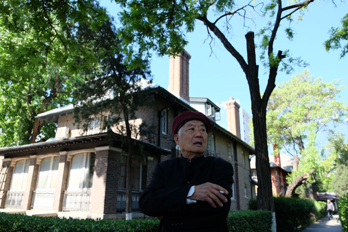 Li Zhengrong, 74, stands in front of one of the buildings of the quarters for doctors and nurses who work at one of Beijing's oldest hospitals, the Peking Union Medical College Hospital, which was built by the Rockefeller Foundation in 1921. Photo: Wu Gang/Caixin