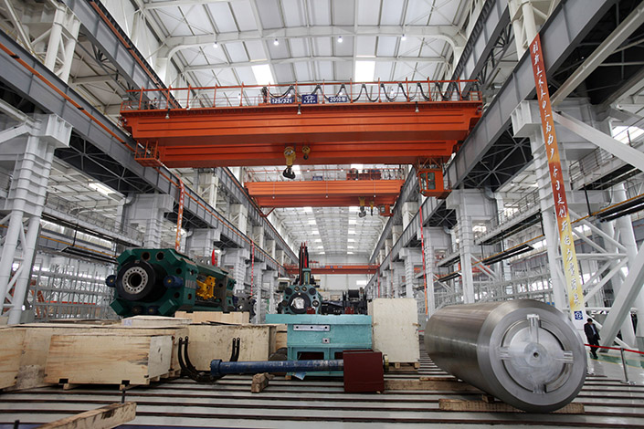An employee walks past heavy equipment in a research and development center in Tianjin Binhai New Area, on April 27, 2012. Tianjin plans to allow employees to buy shares of state-owned enterprises. Photo: Visual China