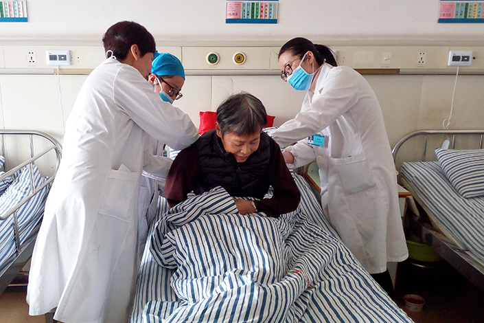 New Chinese government guidelines say that all public hospitals by September must stop adding medicine surcharges to patients' bills, and they cannot raise fees by more than 10% this year. Above, medical staff attend to a patient in a hospital in Jiaxing, Zhejiang province, on March 29. Photo: Visual China