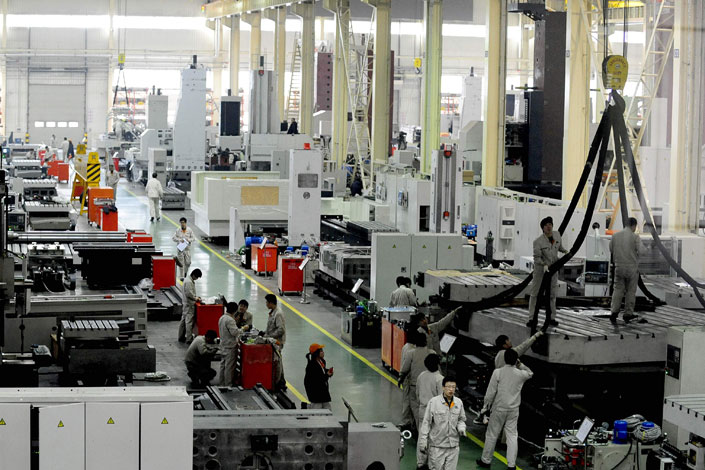 Employees work at a Shenyang Machine Tool Co., Ltd plant on Feb. 21, 2011。China Construction Bank has thrown the loss-making machinery maker a 10 billion yuan lifeline. Photo: Visual China