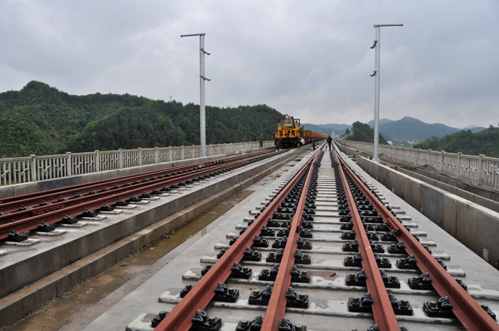 China Railway Corp. is leasing eight new express cargo trains in a bid to reduce debt and boost profitability. Above, construction workers lay high-speed-rail tracks in Shangrao, Jiangxi province, on April 26, 2014.  Photo: Visual China