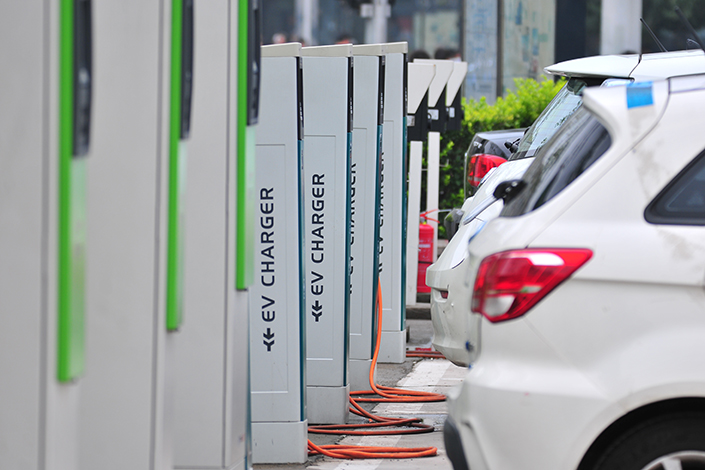 Cars line up at a new energy electric vehicle charging station in Zhongguancun Street in Beijing, China, on July 22, 2016. WKW Auto Parts plans to invest in a production base to develop and build high-quality new energy vehicles in Germany. Photo: Visual China