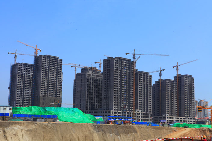 Construction work is carried out on buildings in Rizhao, Shandong province, China, on July 12, 2014. The top 25 land-buying companies spent 494.3 billion yuan in the first four months of this year, nearly double the amount spent in the same period last year. Photo: Visual China